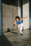 Young female athlete running fast outside in the city. Sporty woman training. - 195043774
