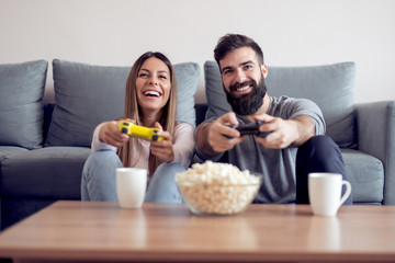 Joyful couple playing video games at home.