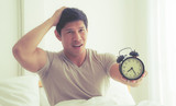 Man woke up late and show alarm clock to the camera