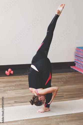 Aluminium School de yoga Woman makes the yoga exercise on the mat, indoors