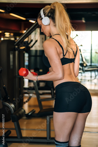 beautiful blonde woman working out in the gym training lifting weights listening music