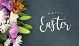 Fototapety Spring season still life with Happy Easter calligraphy holiday script over dark blackboard background texture with beautiful colorful white, pink, orange, purple and green flower blossom bouquet