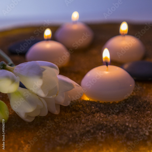 burning candles, stones and white flowers