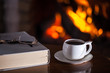 White cup of tea or coffee, glasses and old book near fireplace on wooden table. Winter and Christmas holiday concept