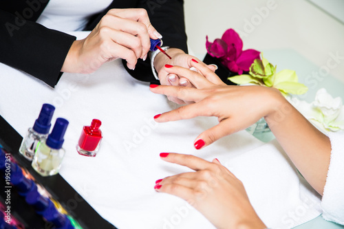 Fotobehang Manicure мастер делает маникюр клиентке. руки с красным маникюром на фоне флаконов лака для ногтей