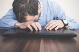 Caucasian tired businessman sleeping over a laptop.