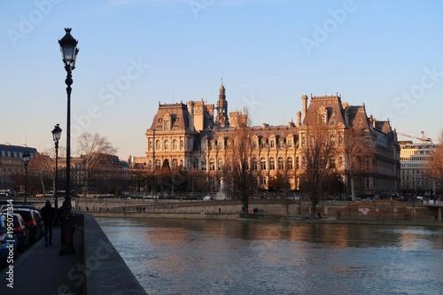 Poster Parijs Vue sur l'Hôtel de ville de Paris et la Seine depuis un quai, au soleil couchant (France)