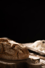 Freshly baked bread on wooden table on dark background