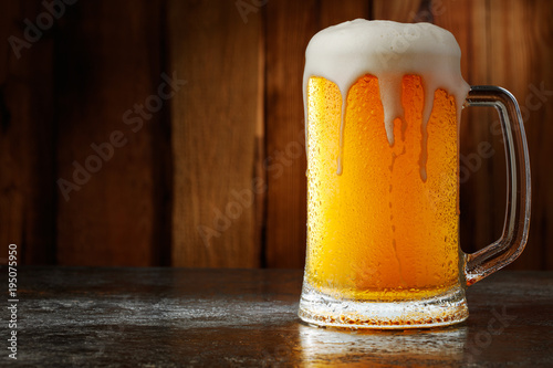 Fototapeta mug with beer on a wooden background