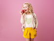 happy modern child isolated on pink eating an apple