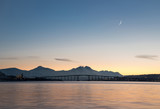 NORWAY, TROMSO - JANUARY 18, 2018: Panoramic view of arctic town Tromso during beautiful dusk with mountains and horned moon background