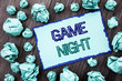 Conceptual hand writing text showing Game Night. Concept meaning Entertainment Fun Play Time Event For Gaming written on Sticky note paper folded paper on the wooden background.