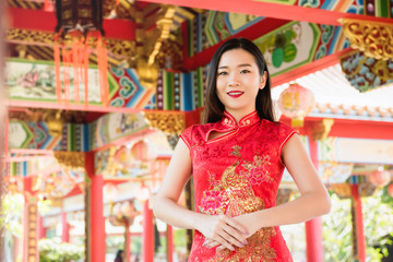 Asian woman in traditional red cheongsam qipao dress at Chinese temple