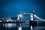 the iconic Tower Bridge of London lit up at night over the River Thames - 195104198