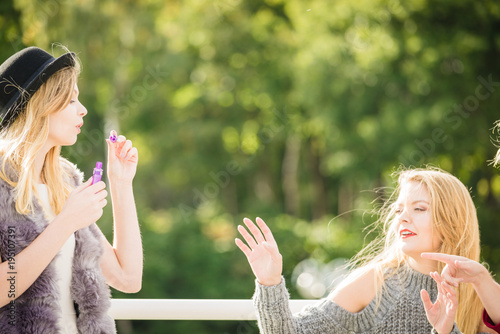 Women friends blowing soap bubbles.