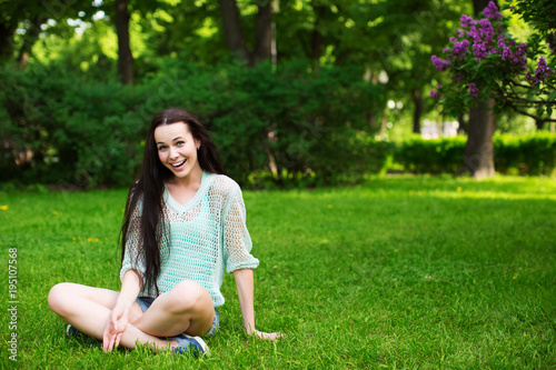 Smiling beautiful young woman  sitting on grass.