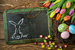 Eastern bunny on blackboard decorated with tulips