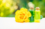Floral essential oils and fragrant rose. Rose oil and a white towel. Spa concept. Aromatherapy and massage. - 195111324