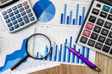 Business graph with magnifying glass and calculator pen on table - 195120302