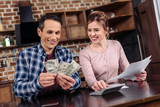 portrait of happy couple counting money together at home - 195122706