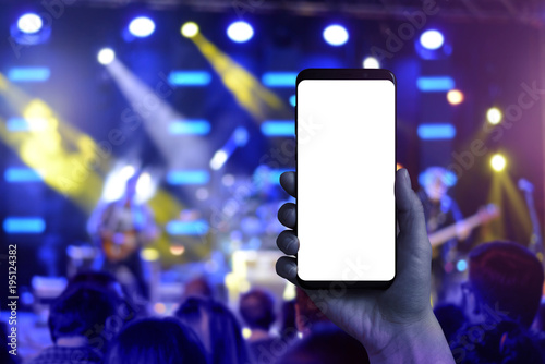 Fototapeta Taking photos of music concert with a mobile phone. Isolated screen for mockup.