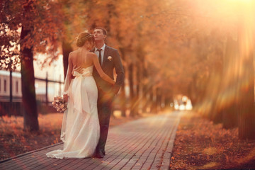 Newlyweds groom and bride walking in autumn park