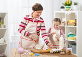 Mother and daughter cook at home. Making cookies, kitchen interior, healthy food concept - 195125912