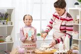 Mother and daughter cook at home. make the dough for buns - 195125931