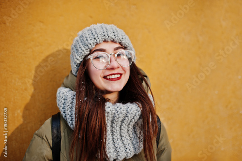 Portrait of brunette girl in gray scarf and hat, glasses at cold weather with sunshine against orange wall of old house. Free copy space. - 195132789