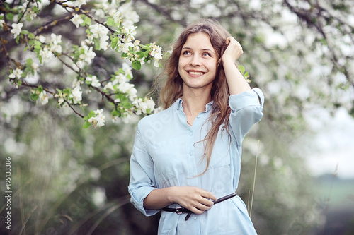 young happy woman walking in an apple orchard in the spring flowers white
