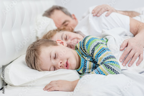 young boy is sleeping with his grandparents on the bed