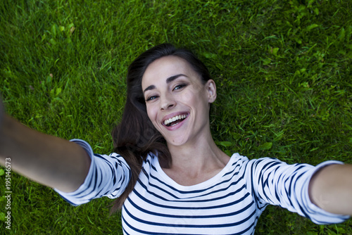 An attractive smiling modern young woman with chic hair and in casual clothes lies on the green grass. View from above