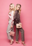 Two beautiful young women in casual clothes posing over pink background.