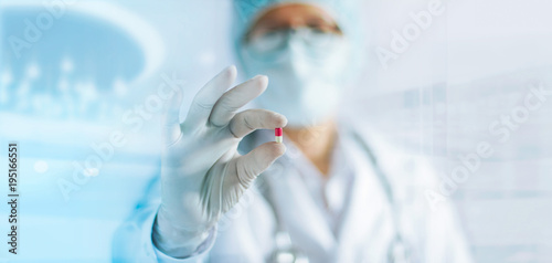 Medicine doctor holding a color capsule pill in hand with white glove in laboratory background © ipopba