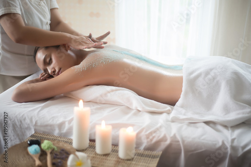 Beautiful woman getting a salt scrub beauty treatment in the health spa. © Johnstocker