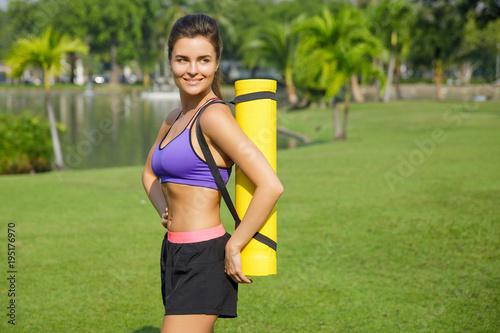 Aluminium School de yoga Woman with a fitness mat in the park
