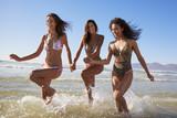 Female Friends Have Fun Running Through Waves On Beach Vacation