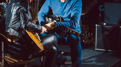 Guitar music teacher helping his student to play, closeup on the hands
