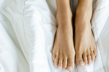 Female feet on the soft bed linen