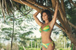 Sexy and beautiful woman is posing in shade of tropical trees