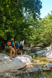 Tourists walk along the rocky bank of a mountain river