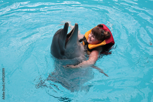 Fototapeta Happy child and dolphins in blue water. Dolphin Assisted Therapy