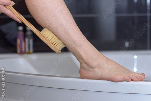 Foto op Canvas Spa Woman scrubbing her leg with a brush