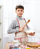 Boy cooking in home kitchen, making dough, healthy food concept - 195216152