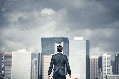Man standing in the big city with storm clouds over head. Conquering adversity, challenging yourself concept.