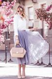 Outdoor fullbody portrait of young beautiful fashionable girl walking in street of european city. Model wearing stylish blouse, skirt, sunglasses, holding pink handbag. Spring, summer  fashion  - 195244965