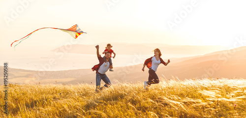 Papiers peints Echelle de hauteur Happy family father, mother and child daughter launch a kite on nature at sunset