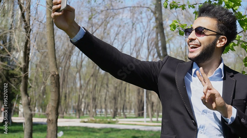 Handsome man bought phone and testing new functions of camera. Happy Arabian showing. Guy has dark hair, beard and wears sunglasses. Concept of modern technologies new functions in smartphones and