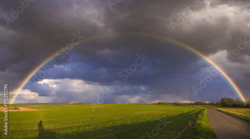 Aluminium Lente Rainbow over the spring field after the evening storm