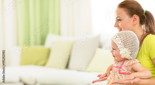 Happy mother and kid sitting together on sofa in living room
